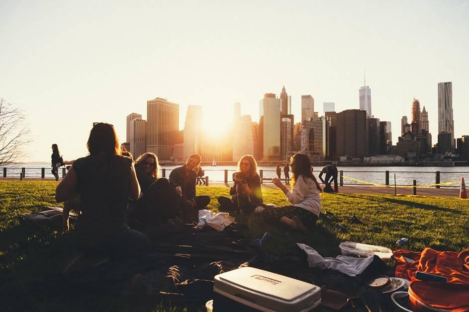 Mladi ljudi prave piknik u prirodi pored grada
