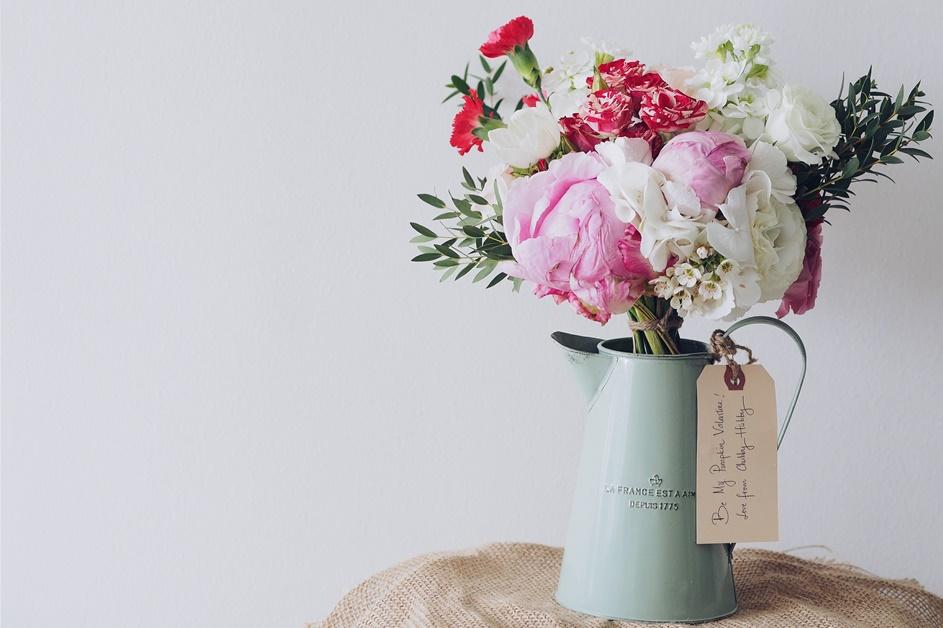 Buket cveća koji stoji u metalnoj vazi svetlo zelene boje