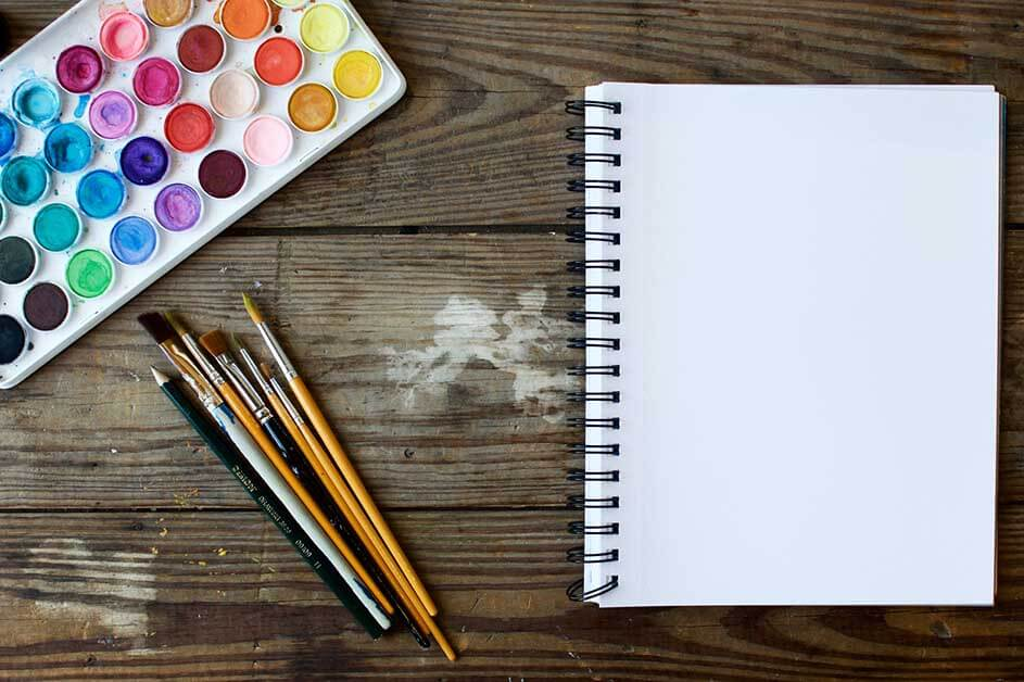 Sveska i olovke na drvenom stolu