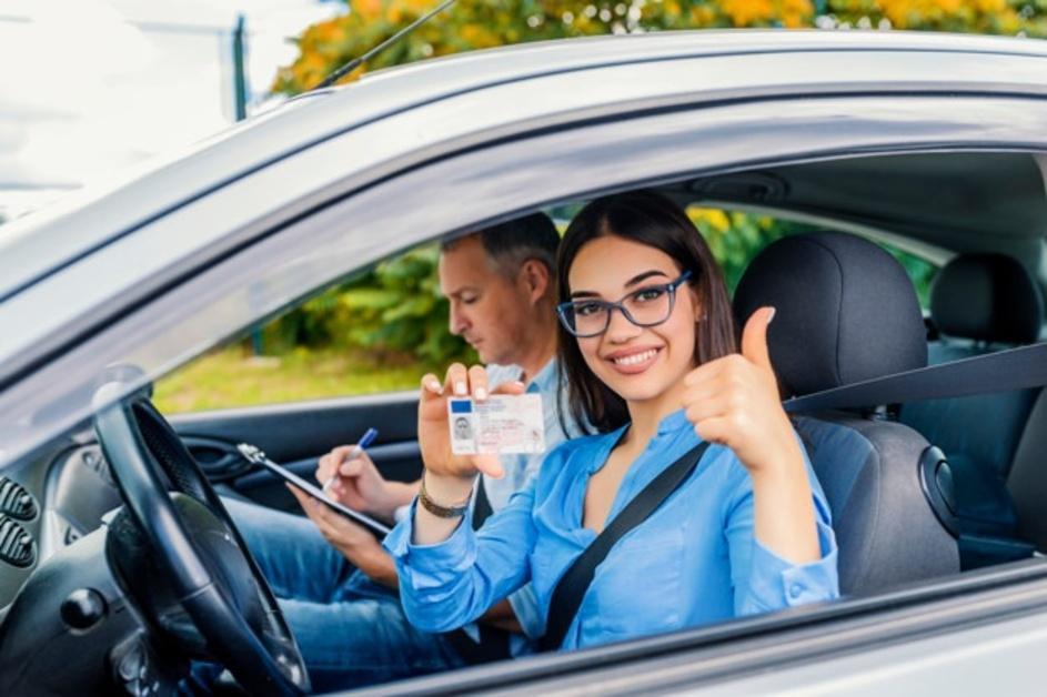Prikaz devojke koja sedi na prednjem sedištu automobila pokazujući svoju vozačku dozvolu